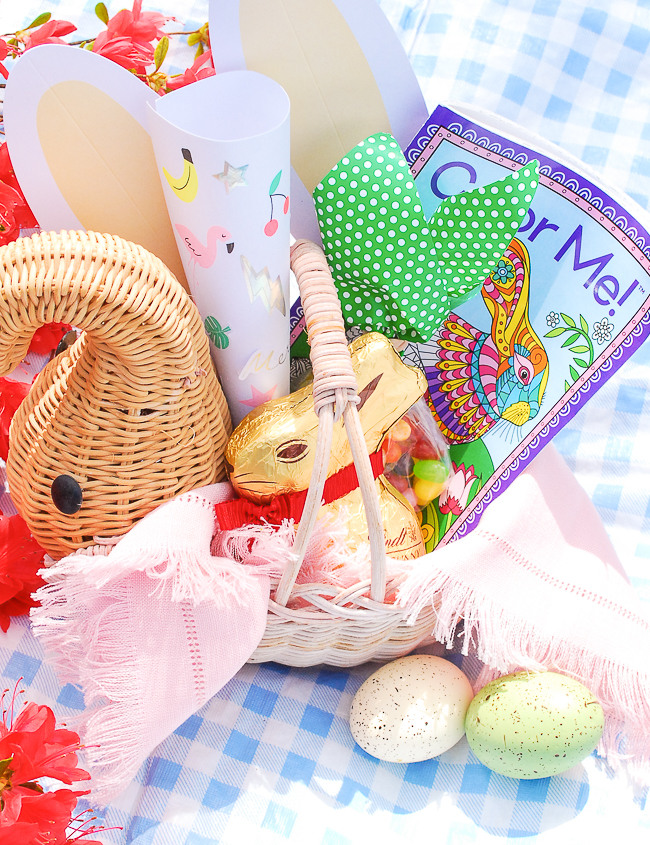 Easter basket for kids using vintage wicker elephant filled with coloring books, stickers, bunny ears, and chocolate bunnies.