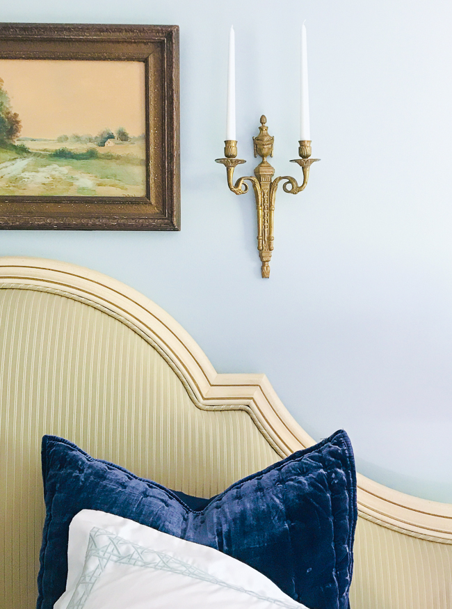 Estate sale find - upholstered headboard in striped silk with neoclassical candle sconce and water color landscape above.