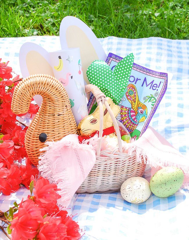 Vintage wicker elephant for kids Easter basket inspiration filled with coloring book, bunny ears, stickers, and chocolate bunny.