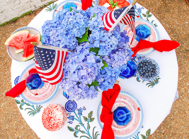 Top view of patriotic table decor with blue hydrangea and US flag centerpiece, red and blue antique china, blue Independence goblets, and Indian block print tablecloth