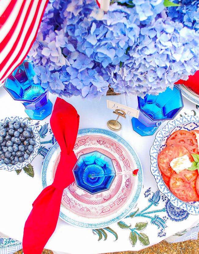 July 4th place setting with blue rice eye dinner plates, red willow salad plates, and blue glass goblets