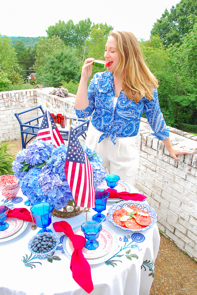 Katherine enjoying watermelon with her 4th of July tablescape