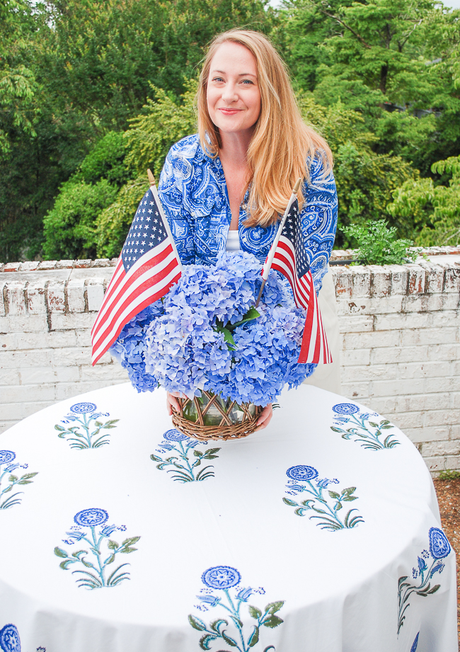 Katherine places blue hydrangea floral arrangement with US flags in a rustic wicker vase on table
