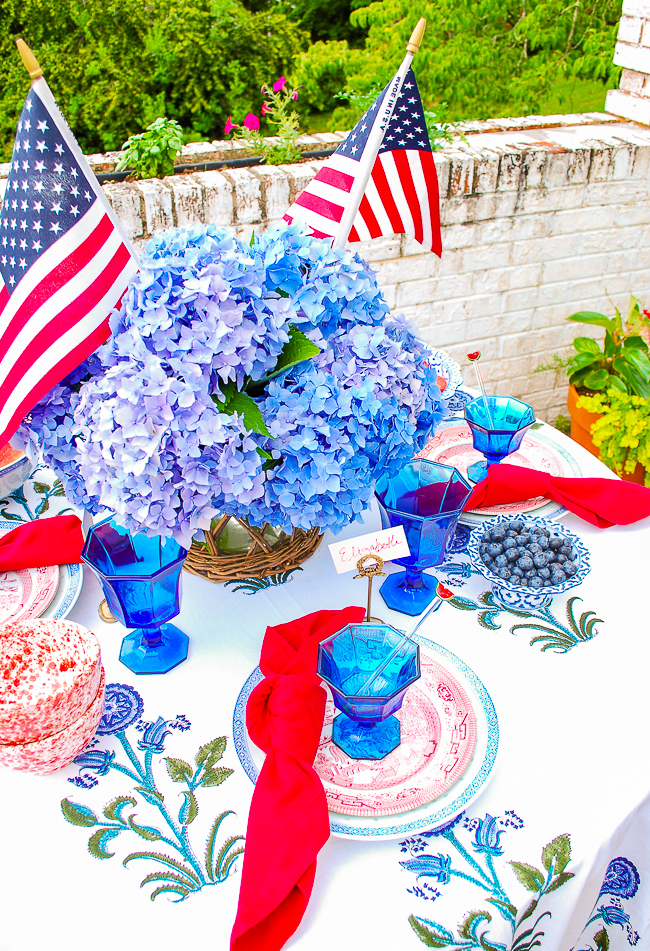 patriotic table decor with blue hydrangea and US flag centerpiece, red and blue antique china, blue Independence goblets, and Indian block print tablecloth