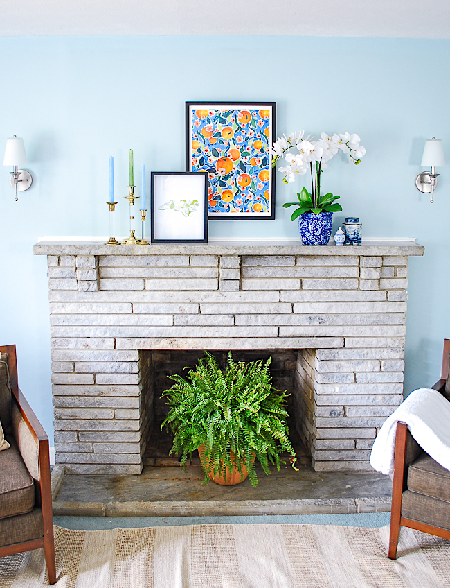 Asymmetrical arrangement for a preppy traditional mantel in blue and white with pops of orange and green