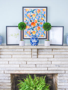 Another important elevated essential of this preppy traditional mantel is natural elements done here with boxwood topiaries and a fern.