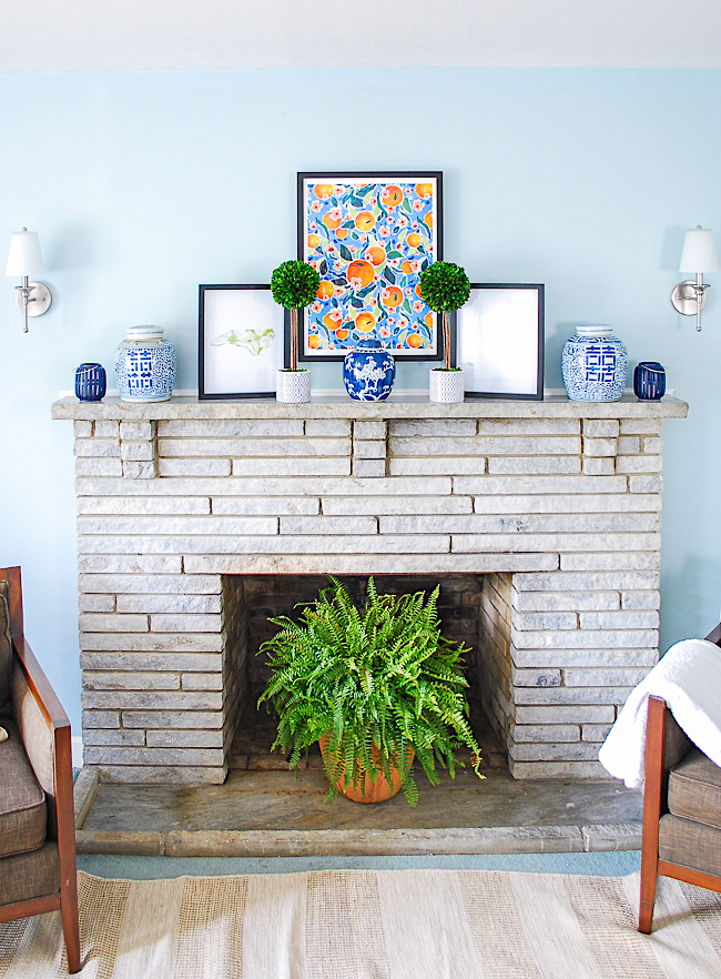 Symmetrical arrangement for a preppy traditional mantel in blue and white with pops of orange and green.