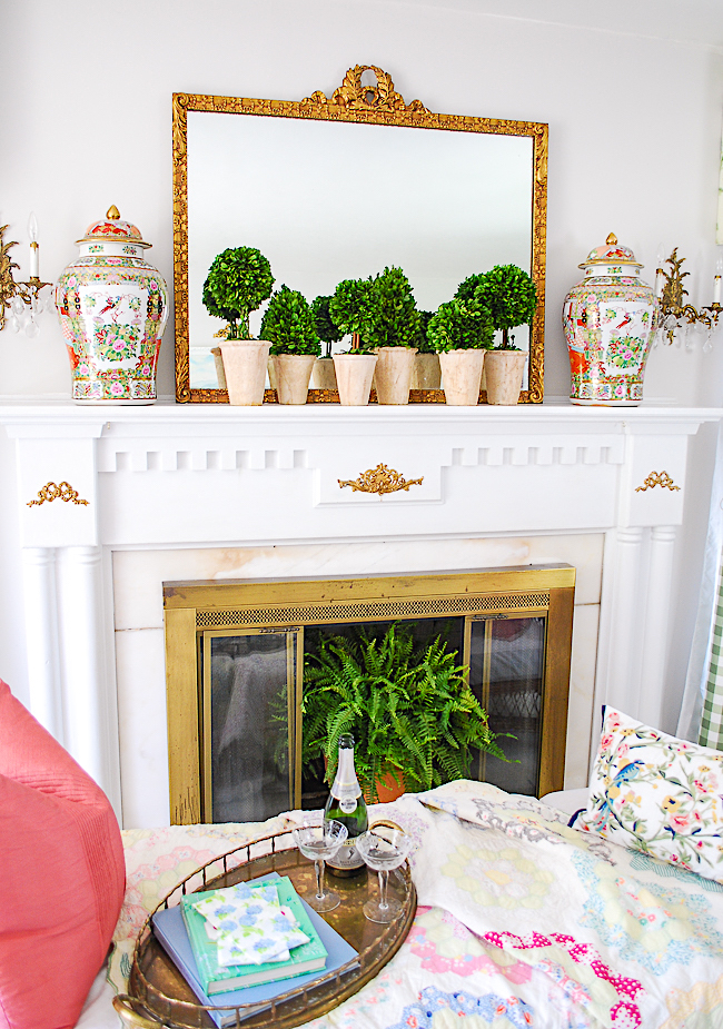 A pair of statement rose medallion ginger jars are the star curios on this mantel