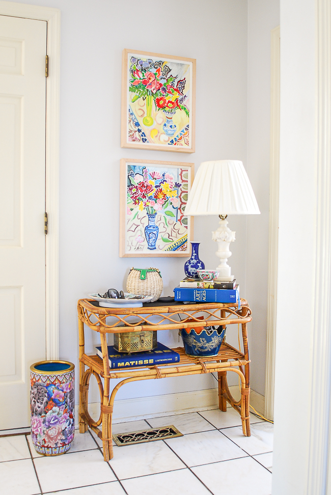 Rattan console table with marble lamp, books, catchalls, and colorful floral paintings above