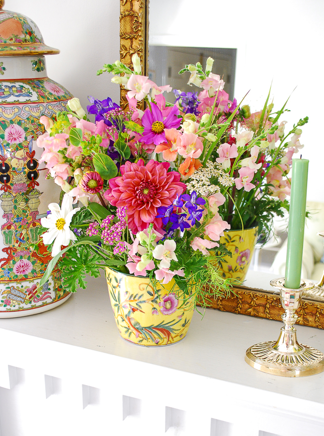 Mixed florals of pink, green, and purple in yellow Chinoiserie vase with silver candlestick on version one mantel