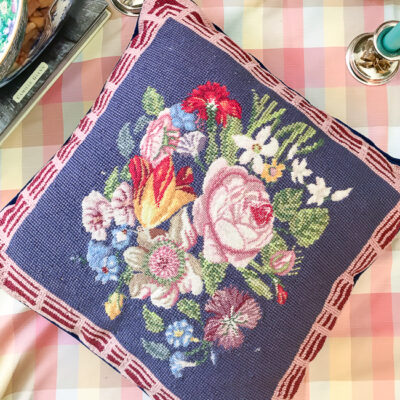 needlepoint pillow with floral spray design, purple background, and pink border