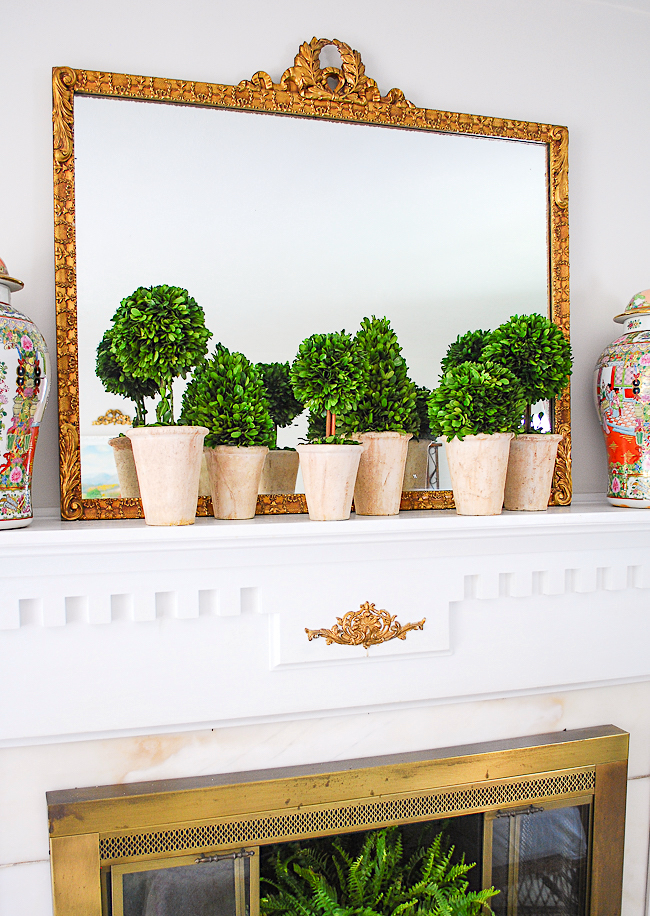 A collection of boxwood topiary nestle along a mantel with gilt mirror and rose medallion temple jars for a grandmillennial look