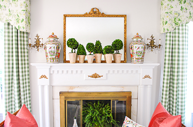 Version two of my grandmillennial style mantel features a collection of boxwood topiary and rose medallion temple jars with gilt mirror