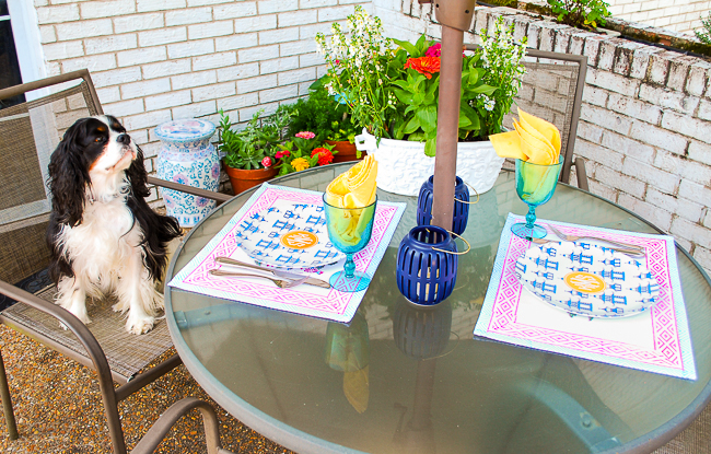 Patio tablescape with colorful placemats, pagoda monogrammed plates, and Henry sitting in chair