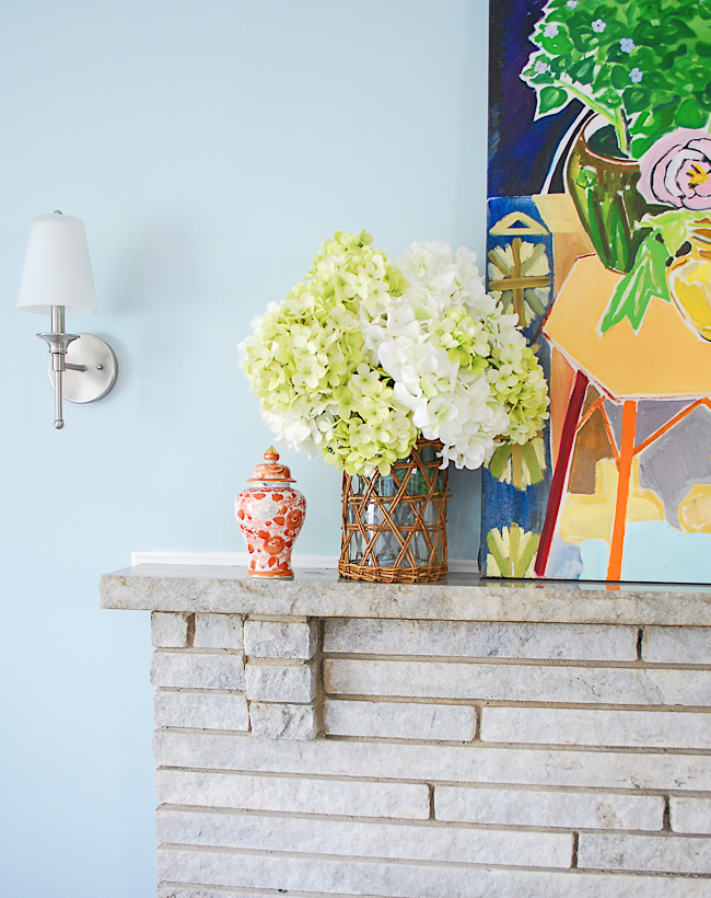 Bright mantel with abstract painting, hydrangea arrangement, and brass candlesticks for summer decorating ideas