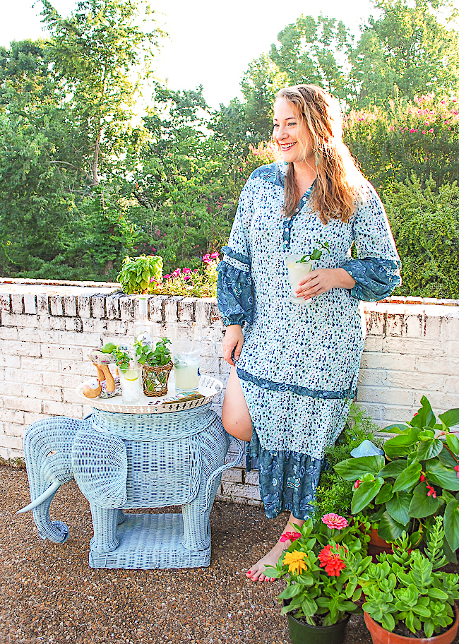 Katherine in blue and green caftan drinking a coconut mojito with wicker elephant bar set up