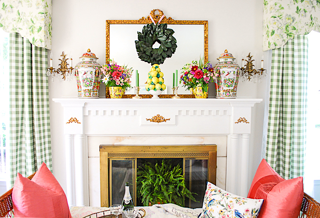 Version one of my grandmillennial mantel features magnolia wreath with ceramic lemon topiary, fresh florals, and rose medallion temple jars