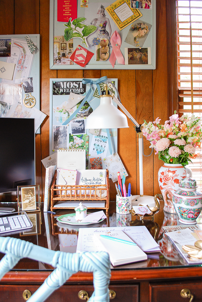 View of Katherine's home office desk with cork boards for inspiration, vintage organizers, and fresh flowers.