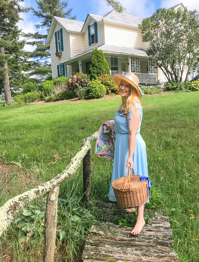 Katherine in blue dress crosses stream in front of Victorian cottage for a picnic