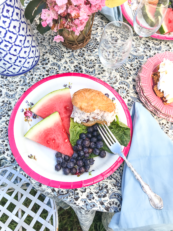 picnic table with plate full of summer fruit and chicken salad on croissant