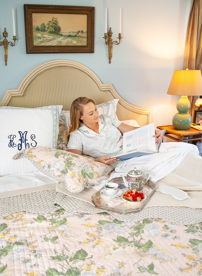 Katherine lounging in bed with pink chintz quilt and silver breakfast tray