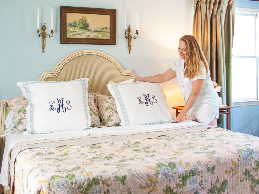 Katherine places monogrammed pillow on bed with grandmillennial bedding