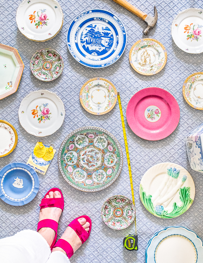 Top down perspective of varied vintage plates laid out on rug with hammer, nails, and measuring tape. Great way to curate a plate wall display.