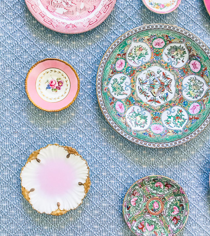 Scalloped edged plates add visual interest to a plate wall display like this pink petal dish