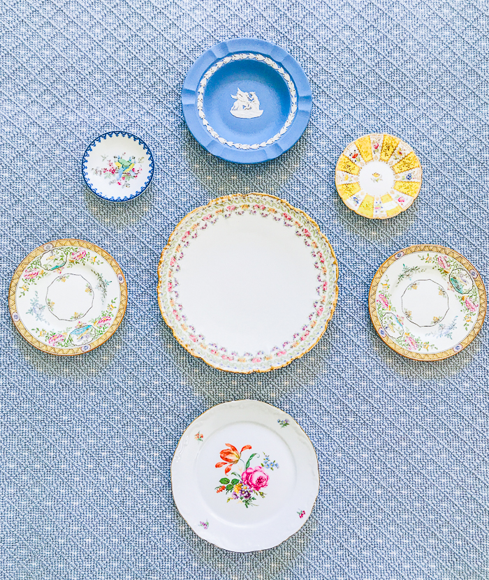 Vintage plates laid out on rug in blues and yellows for a color coordinated plate wall idea.