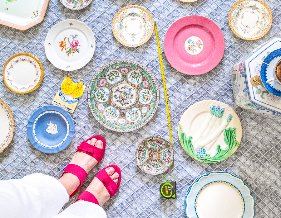 Vintage plates laid out on rug to curate a plate wall with Katherine's feet in the corner.