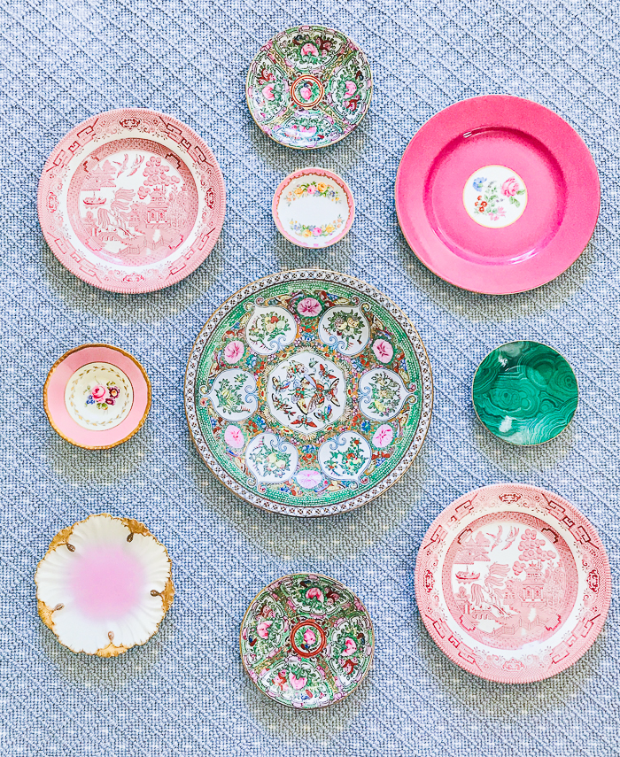 Pink and green vintage plates laid out on rug for curating a plate wall display