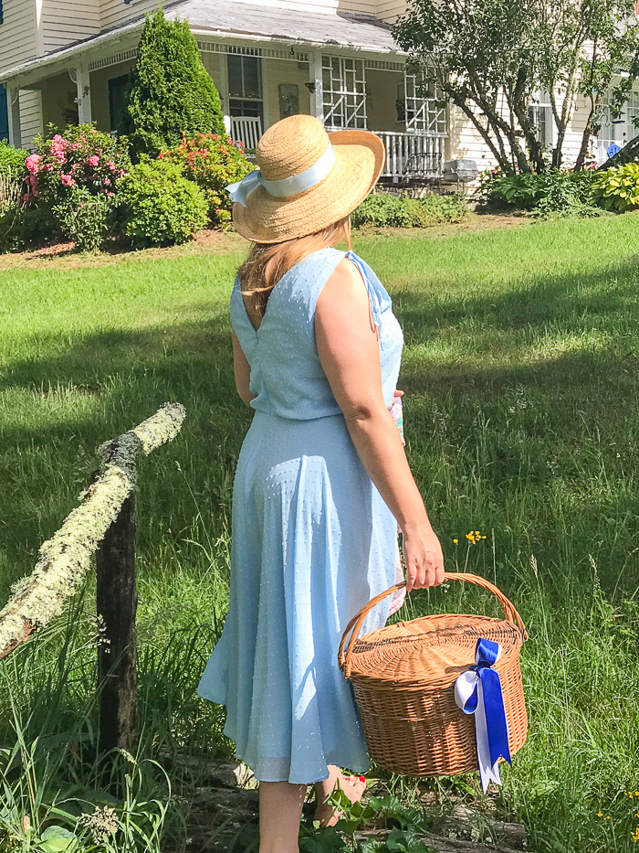 Katherine in blue dress carries picnic basket across stream