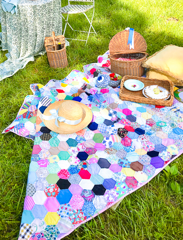 Vintage quilt laid out as picnic basket for a picnic by the pond