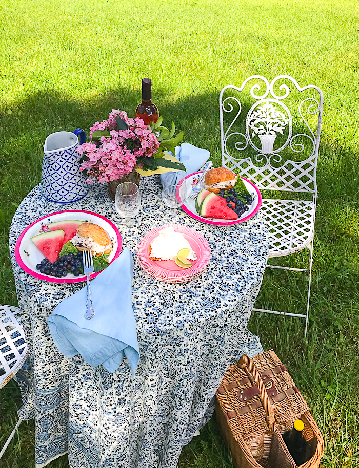 Picnic table set with vintage dishes, cloth napkins, and silver. Plates filled with chicken salad and fruit.