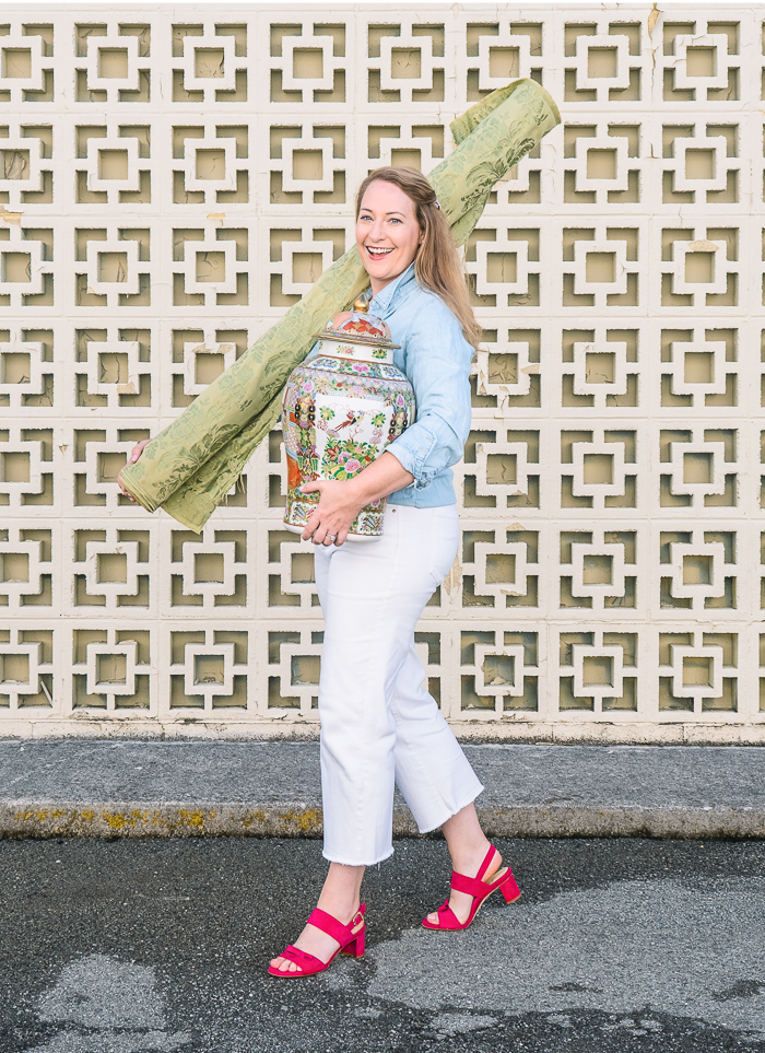 Katherine from Pender & Peony walks down sidewalk toting antiques and fabric for client in casual outfit with white jeans, chambray shirt, and pink sandal