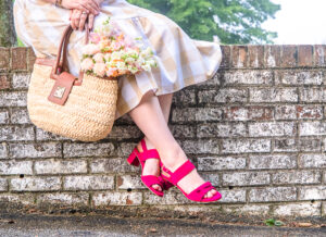 Katherine of Pender & Peony sitting on brick wall in the Nadia pink sandal from Sarah Flint