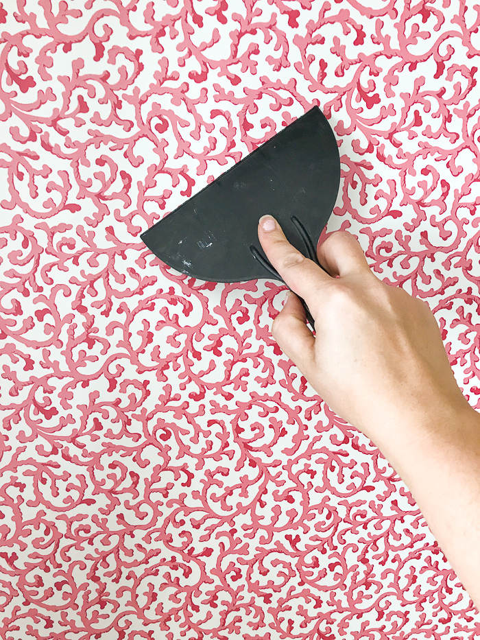 Use squeegee to smooth out wrinkles and air bubbles in wallpaper