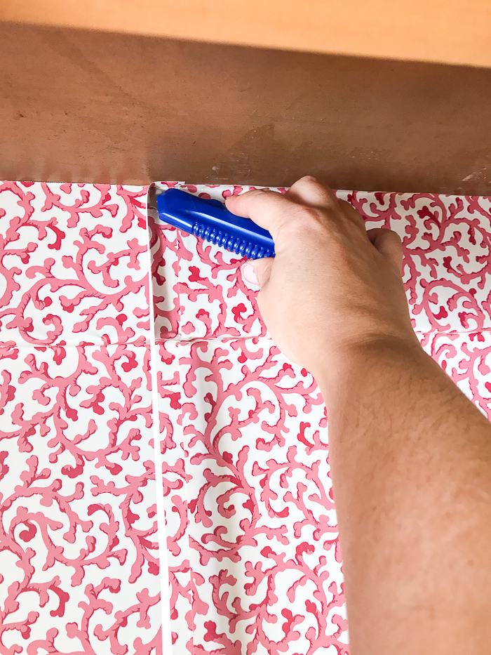 Using a straight razor trim excess wallpaper from top and bottom