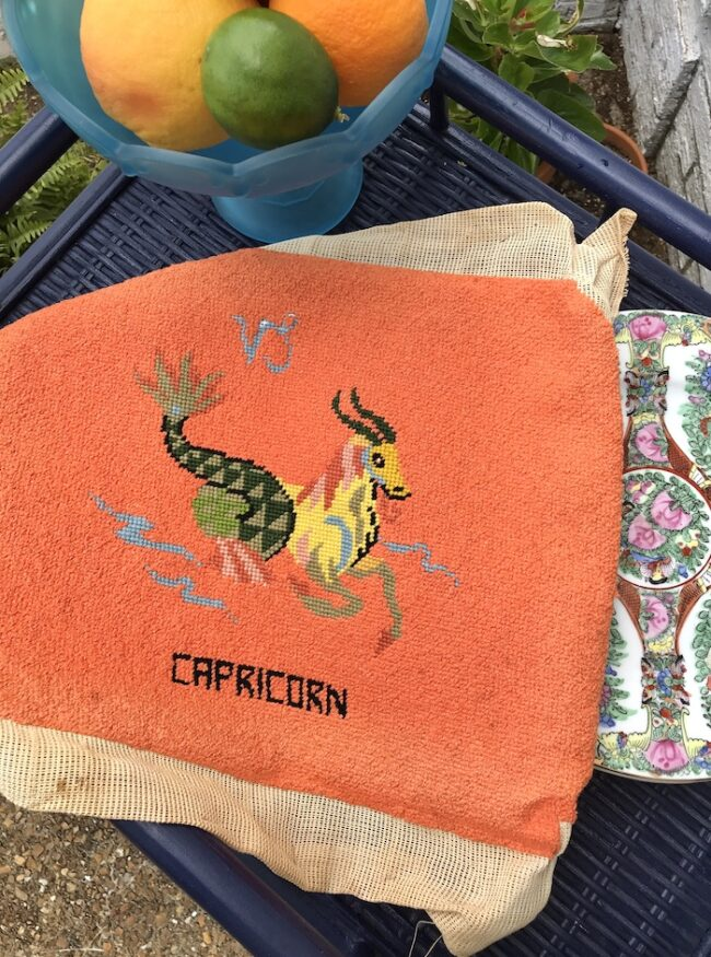 Vintage needlepoint Capricorn symbol with orange background