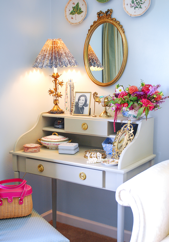 Bedroom corner with vintage vanity styled with gilt mirror, glam lamp, vintage boxes, and flowers.