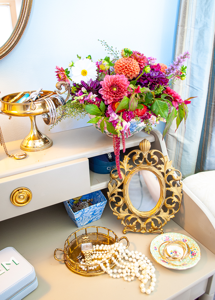 gilt table mirror with pearls arranged in tray and bowl of dahlias on shelf
