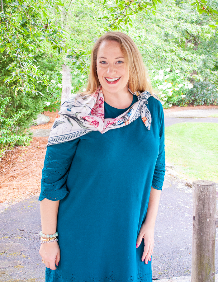 Katherine in teal dress wearing blooming petal scarf from Sarah flint styled in an asymmetrical wrap tie