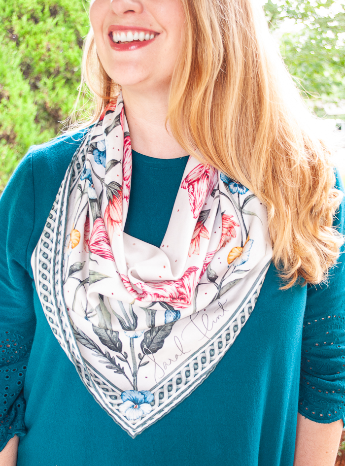 Close up view of Sarah Flint's blooming petal silk scarf tied in cowboy bib style