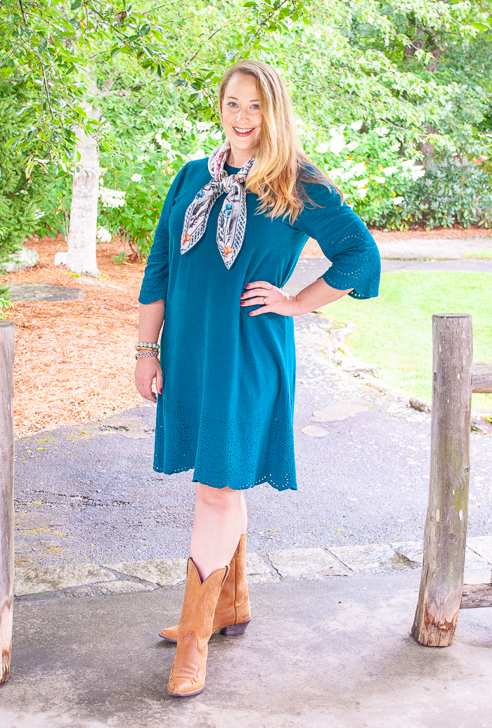 Katherine wears teal dress with brown cowboy boots and silk scarf tied in girl scout style