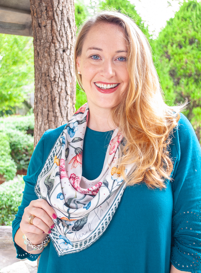 Portrait view of Katherine wearing floral silk scarf tied in cowboy bib style.
