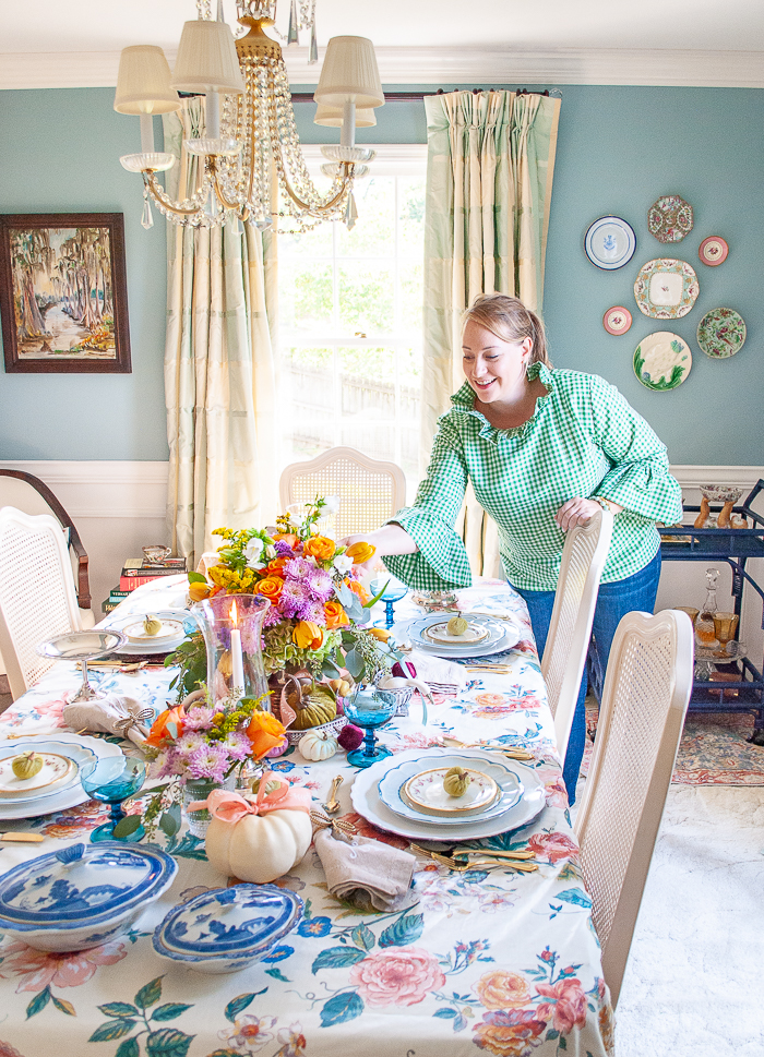 Katherine in green gingham blouse leans over to fix flowers on fall table with pastel hues, chintz tablecloth, candles, white pumpkins, and antique china.