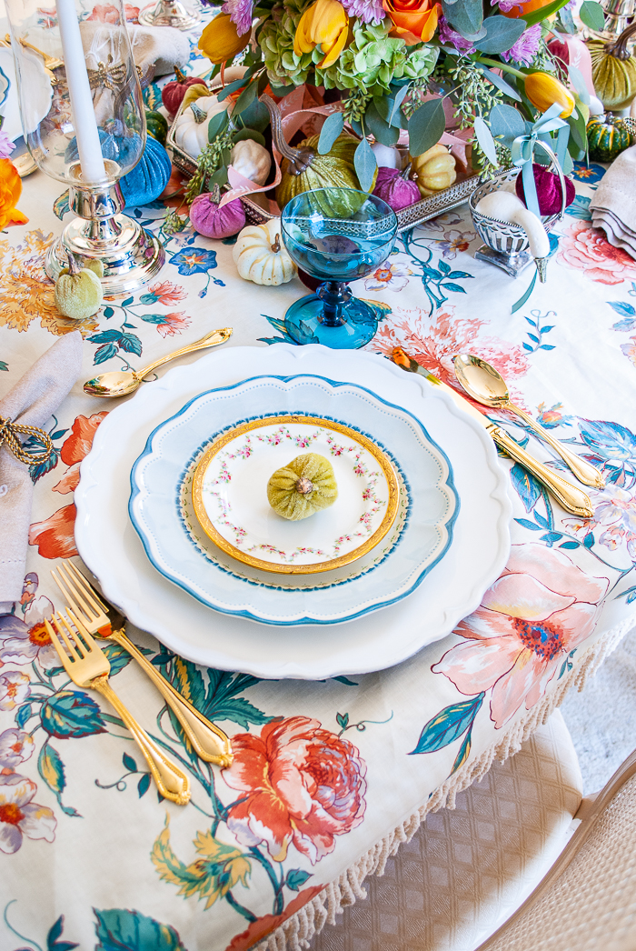 Fall table place setting with blue Lenox plates, rose garland saucers, gold flatware, teal goblet, and mini velvet pumpkin