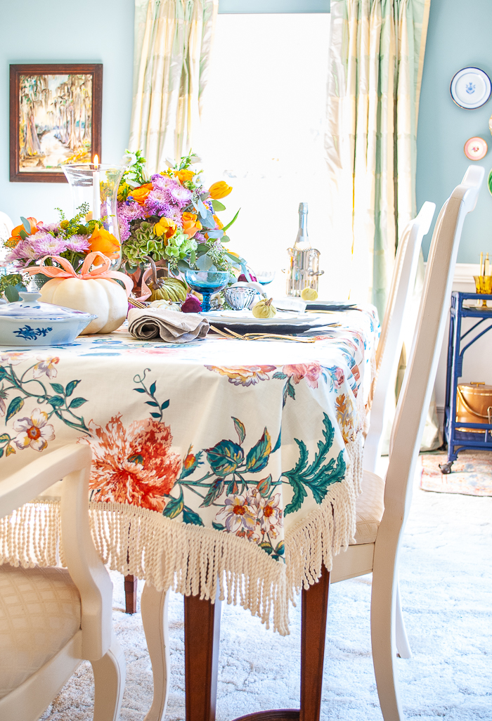 A fall tablescape with DIY pretty chintz tablecloth edged with bullion fringe