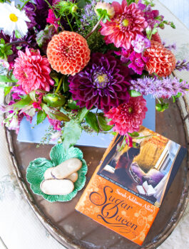 Sugar Queen book by Sarah Addison Allen on brass tray with dahlia floral arrangement and cookies