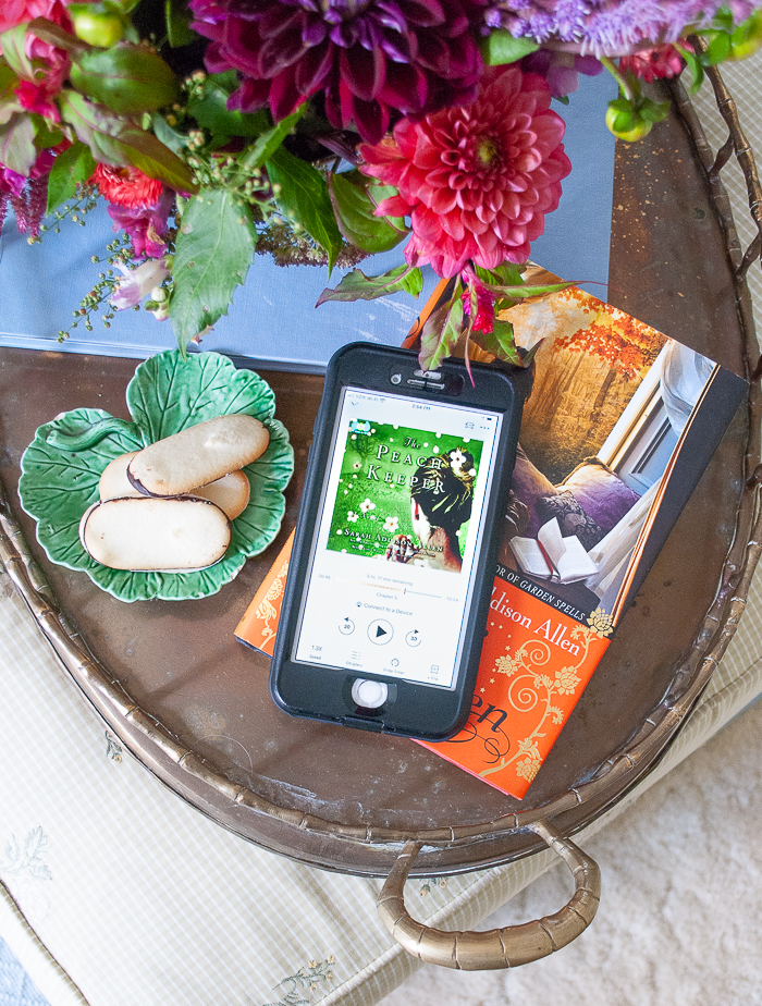Audio book on phone with The Peach Keeper by Sarah Addison Allen on brass tray with dahlia floral arrangement and cookies